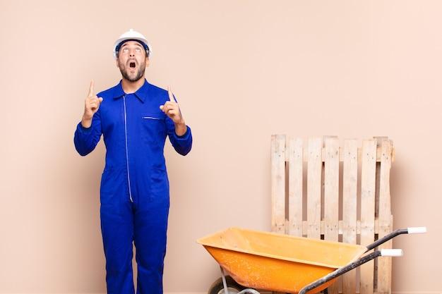 공간 건설 개념을 복사하기 위해 양손으로 위쪽을 가리키는 충격, 놀란 및 입을 벌리고 젊은 남자