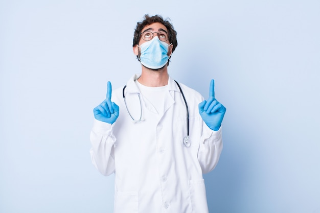 Young man looking shocked, amazed and open mouthed, pointing upwards with both hands to copy space. coronavirus concept