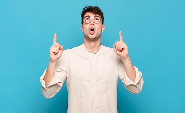 Young man looking shocked, amazed and open mouthed, pointing upwards with both hands to copy space