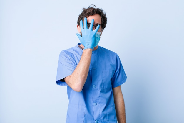 Young man looking shocked, scared or terrified, covering face with hand and peeking between fingers. coronavirus concept