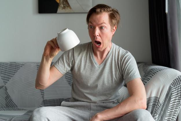 自宅でコーヒーカップを逆さまに保持しながらショックを受けている若い男
