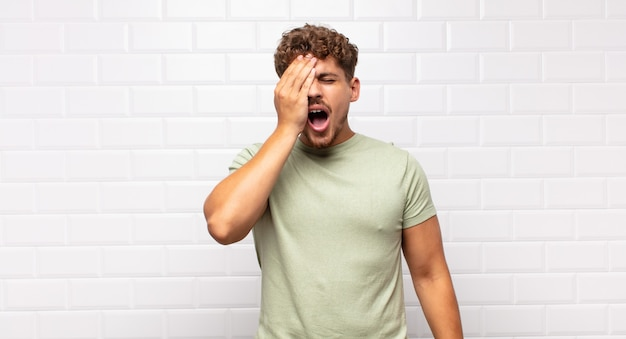 Young man looking sleepy, bored and yawning, with a headache and one hand covering half the face