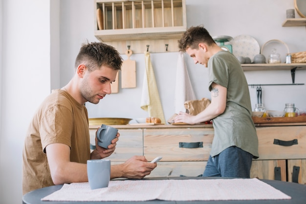 Young man looking at smartphone holding cup while his friend working in kitchen
