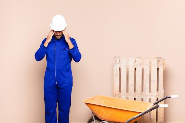 Молодой человек выглядит напряженным и расстроенным, работает под давлением с головной болью и обеспокоен проблемами концепции строительства