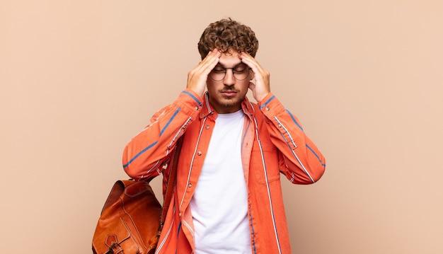 ストレスと欲求不満を見て、頭痛でプレッシャーの下で働いていて、問題に悩んでいる若い男。学生の概念