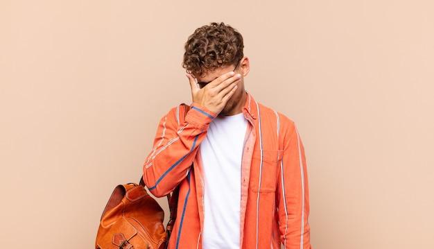 ストレス、恥ずかしがり屋、または動揺して、頭痛で顔を覆っている若い男。学生の概念