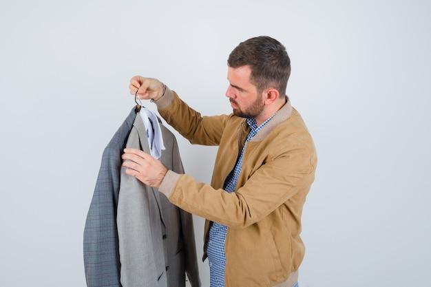 Giovane che guarda gli abiti, in piedi di lato in giacca, camicia e sembra serio.
