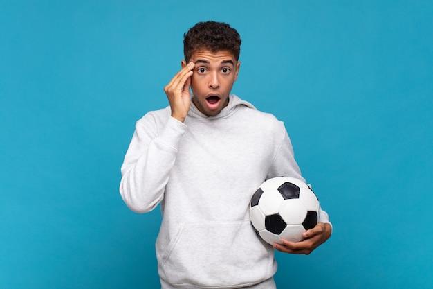 驚いた、口を開いた、ショックを受けた、新しい考え、アイデア、または概念を実現している若い男。サッカーのコンセプト