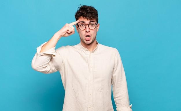 Молодой человек выглядит удивленным, с открытым ртом, шокированным, осознающим новую мысль, идею или концепцию
