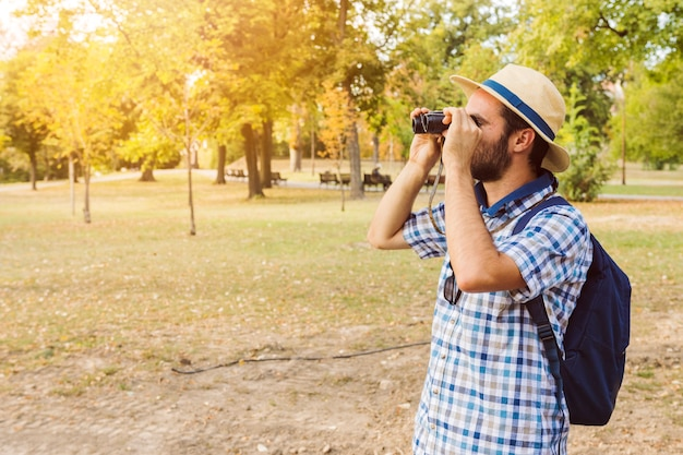Young man looking through binoculars in park