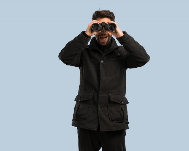 Young man looking through the binoculars
