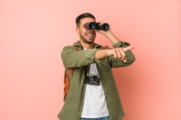 Young man looking through a binoculars.