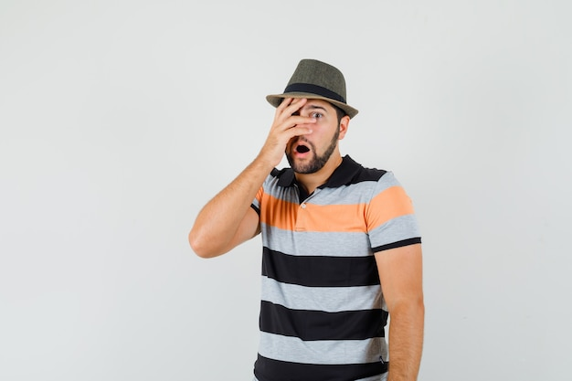 Young man looking through fingers in t-shirt, hat and looking shocked. front view.