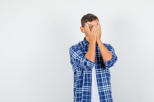 Молодой человек смотрит сквозь пальцы одним глазом в рубашке и выглядит застенчиво, вид спереди.