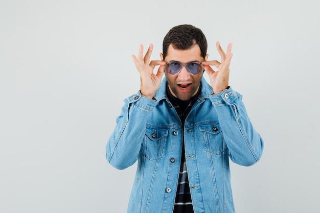 Tシャツ、ジャケット、自信を持って眼鏡を通して見ている若い男。