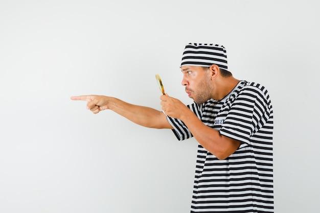縞模様のtシャツの帽子で離れて指している拡大鏡を通して見ている若い男