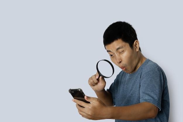 灰色の背景にスマートフォンで虫眼鏡を通して見ている若い男。