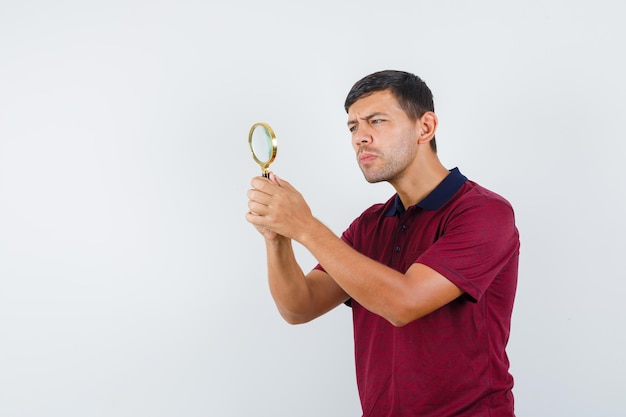Young man looking through magnifying glass in t-shirt front view.