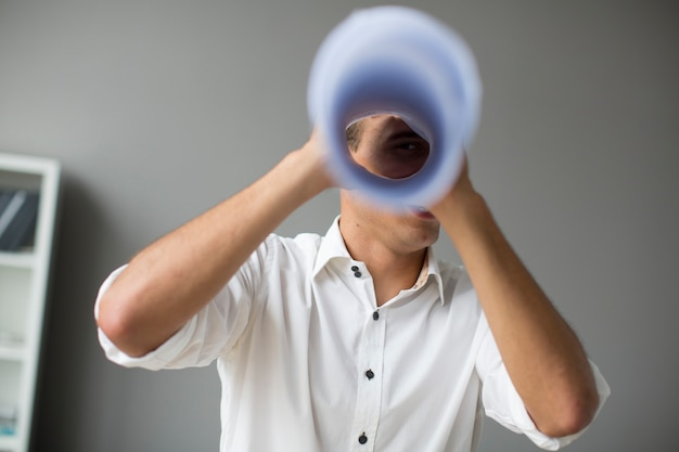 Young man looking through a spyglass