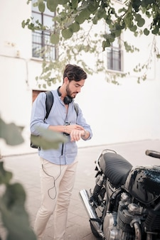Young man looking at time on watch near his motorbike