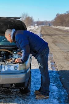 Молодой человек смотрит под капот разбитой машины в холодный зимний день
