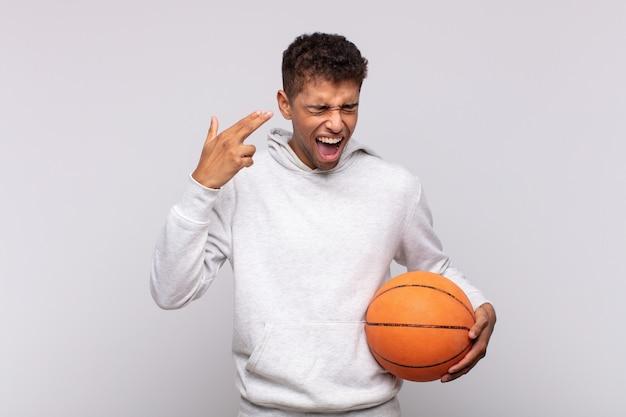 不幸でストレスを感じている若い男、頭を指して、手で銃のサインを作る自殺ジェスチャー。バスケットコンセプト