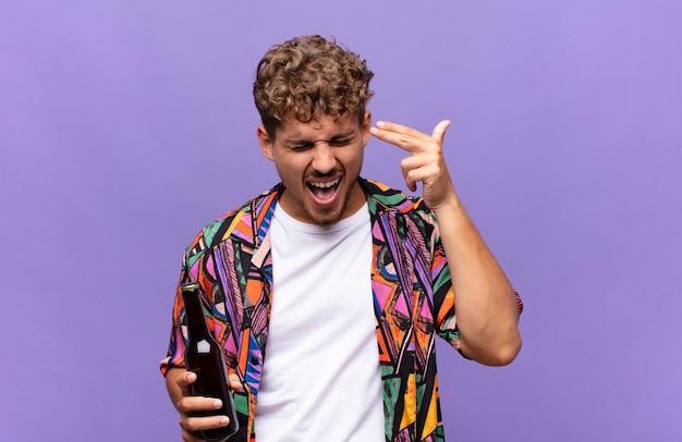 不幸でストレスを感じている若い男、手で銃のサインを作る自殺ジェスチャー、頭を指しています。休日の概念