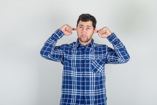 Молодой человек смотрит вверх и затыкает уши пальцами в клетчатой рубашке