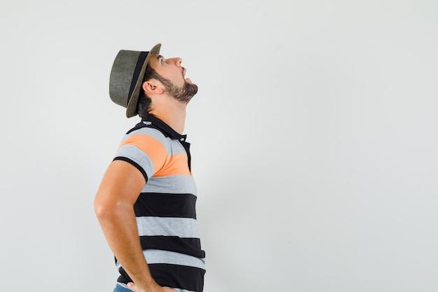 젊은 남자 찾고, t- 셔츠, 모자에 허리에 손을 잡고 잠겨있는 찾고. .