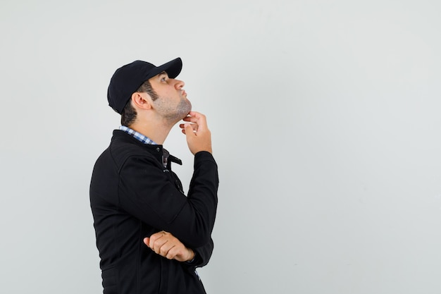Young man looking up in thinking pose in shirt, jacket, cap .