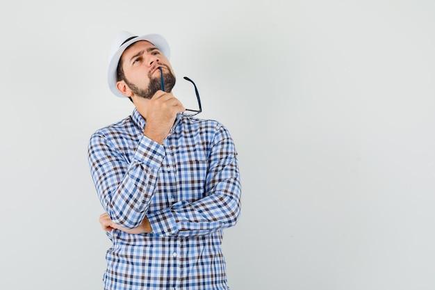 チェックシャツ、帽子、物思いにふける、正面図で眼鏡を噛みながら見上げる若い男。