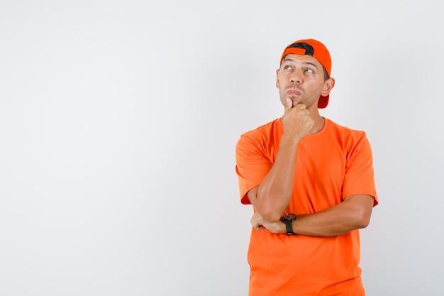 Молодой человек смотрит вверх с рукой на подбородке в оранжевой футболке и кепке и выглядит задумчивым
