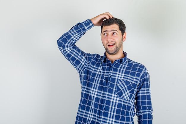 Молодой человек смотрит с рукой на голову в клетчатой рубашке и выглядит мечтательно.