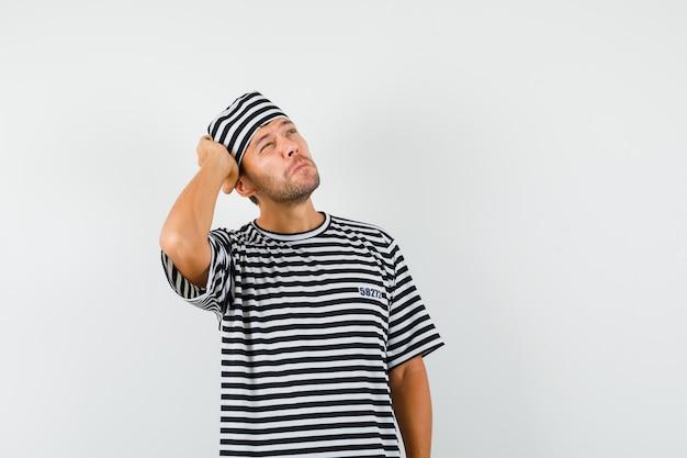 스트라이프 티셔츠 모자에 머리에 손을 올려 잠겨있는 찾고 젊은 남자