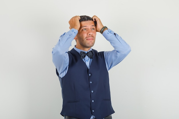Молодой человек смотрит вверх с руками на голове в костюме и выглядит напряженным.