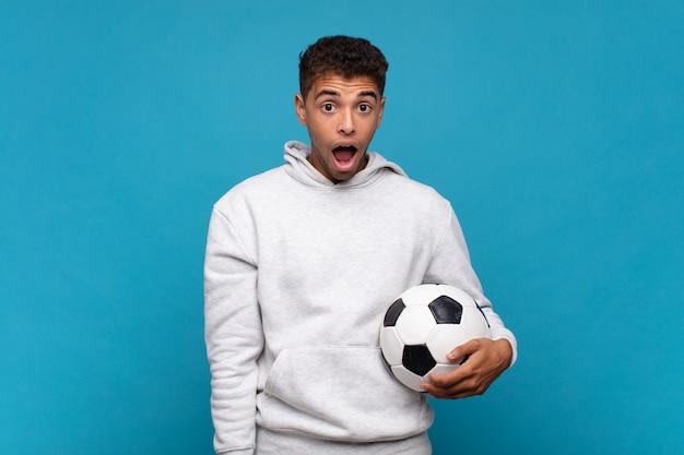 젊은 남자는 매우 충격을 받거나 놀란 표정으로 입을 벌리고 와우라고 말합니다. 축구 개념