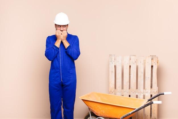 Молодой человек выглядит обеспокоенным, встревоженным, напряженным и испуганным, кусает ногти и смотрит на концепцию строительства бокового пространства