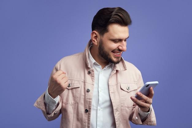 Молодой человек смотрит на экран смартфона, торжественно сжимает кулак