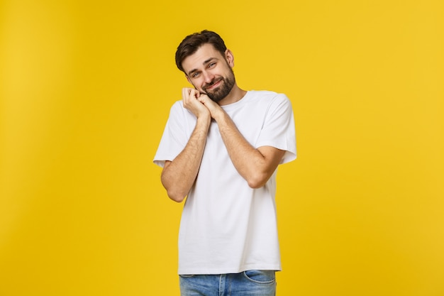 Young man looks to the camera and smiles shy he's got his hands on cheek isolated, with a beard and a  t-shirt