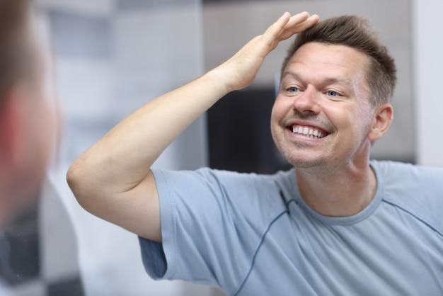 Молодой человек смотрит в зеркало и поправляет волосы рукой