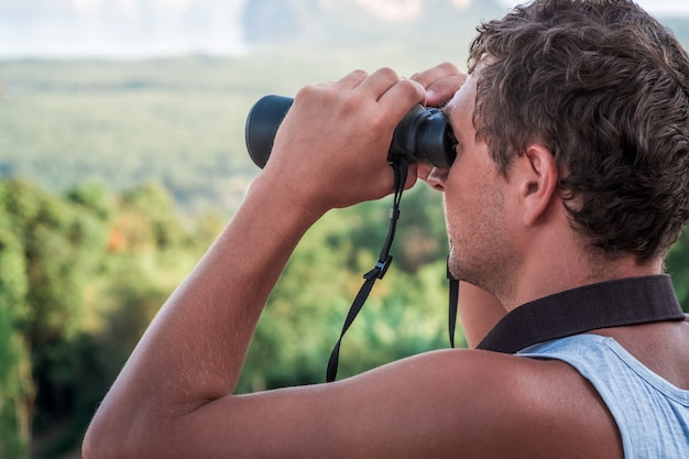 A young man looks into the distance through binoculars.