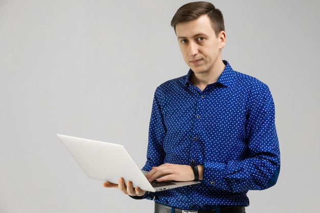 Young man looks at laptop screen in his hands and stands isolated on light