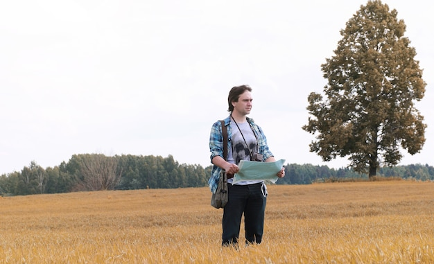 A young man looks at a map autumn season
