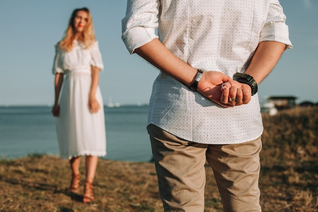 A young man in love is preparing to make his girlfriend an offer to marry, hiding the ring behind his back.