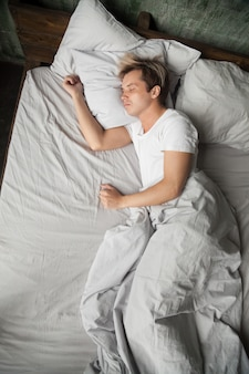 Young man lying asleep sleeping on bed alone, top view