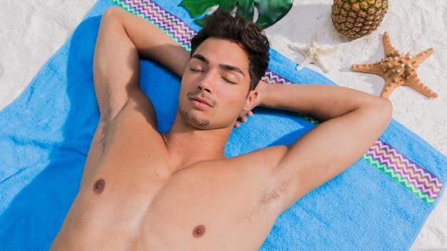 Young man lying on beach