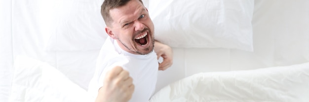 Young man lying in bed and rejoicing top view insomnia treatment concept