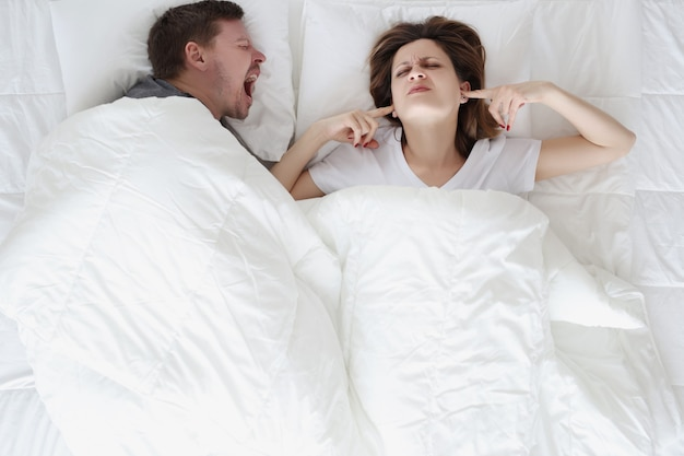 Young man lying in bed and shouting at woman with closed ears top view
