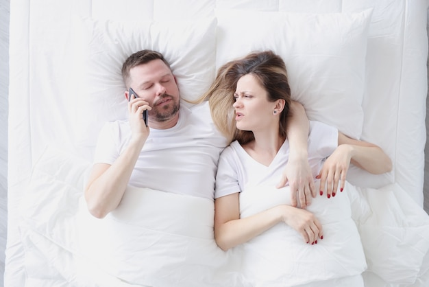 Young man lying in bed with his wife and talking on cell phone top view suspicion of treason