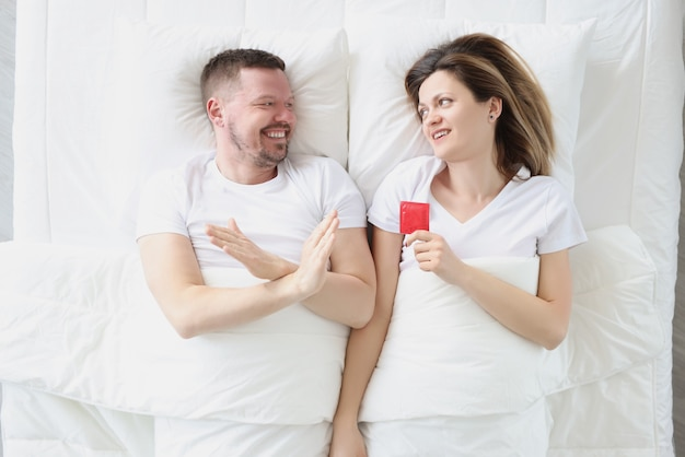 Young man lying in bed with woman and refusing condom top view problems with potency in men